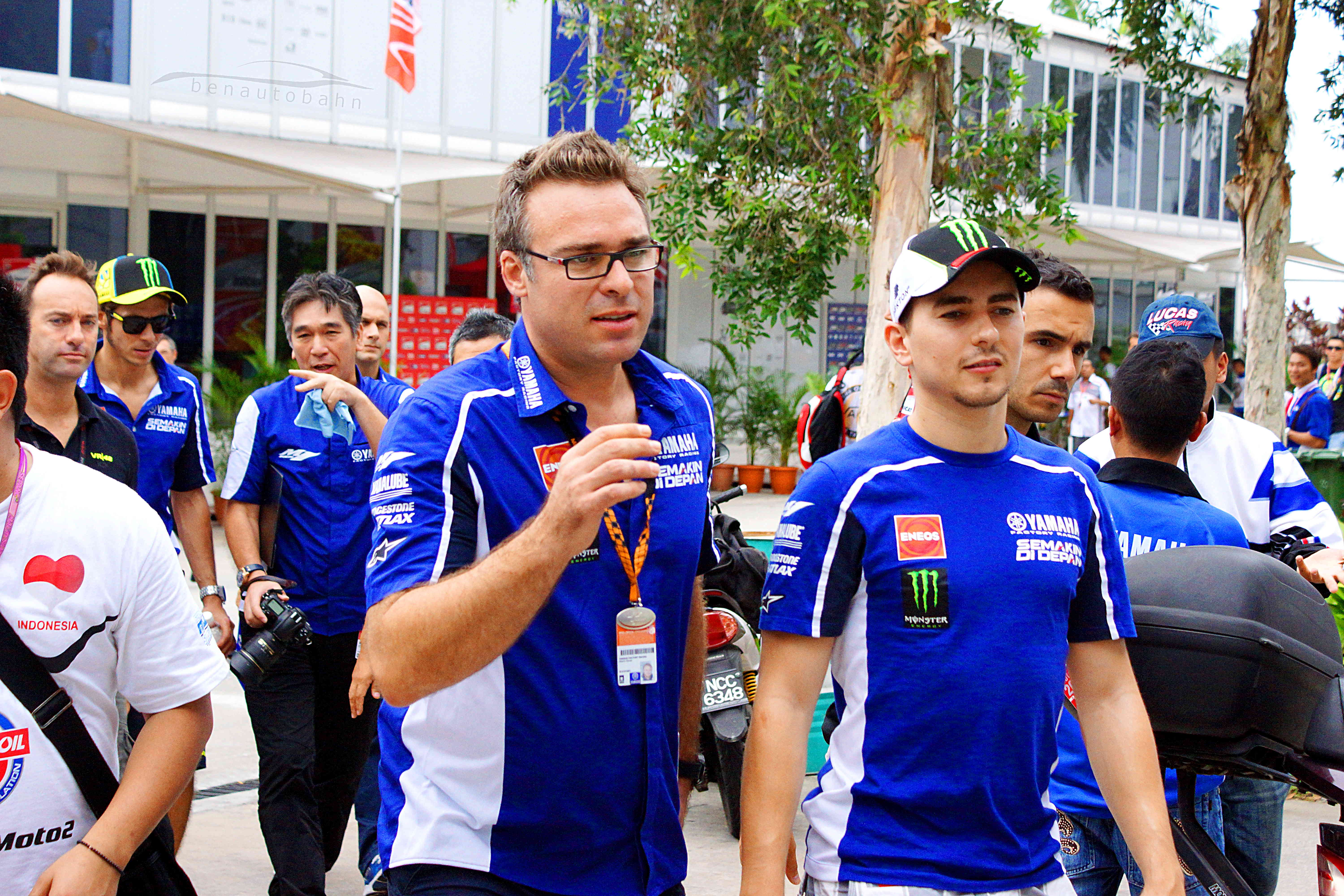 Jorge Lorenzo (right), and Valentino Rossi (rear left, both wearing caps) chatting with their team.